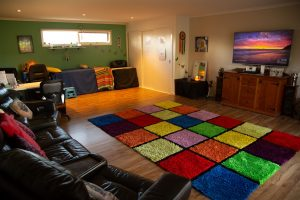 Studio Room at Rainbow Light Therapies showing multicoloured rug, Reiki Table, Desk and Reclining Couch.