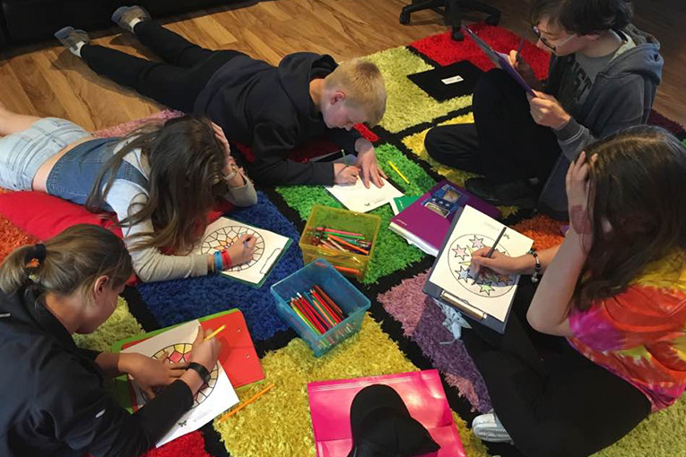 6 Teens sitting and laying on floor completing a worksheet outlining strategies on how to manage stress and anxiety